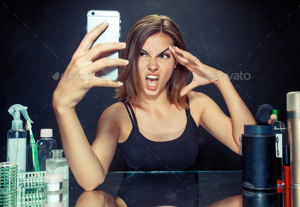Beauty woman with makeup. Beautiful girl looking at the mobile phone and making selfie photo - Stock Photo - Images