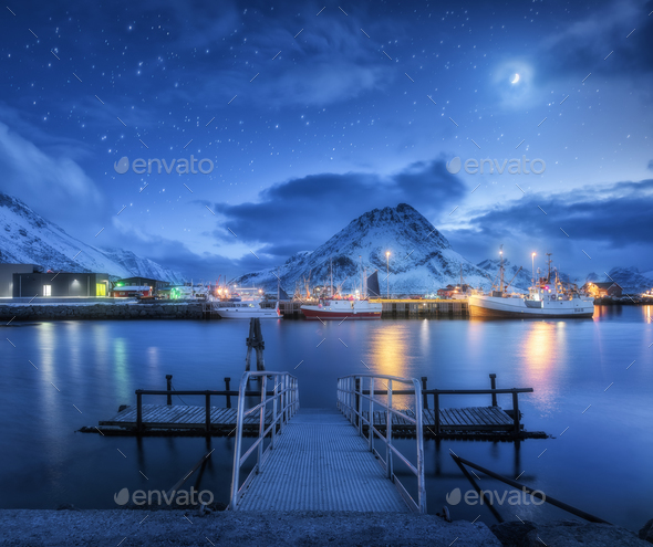 Fishing boats near pier on the sea and snowy mountains at night - Stock Photo - Images