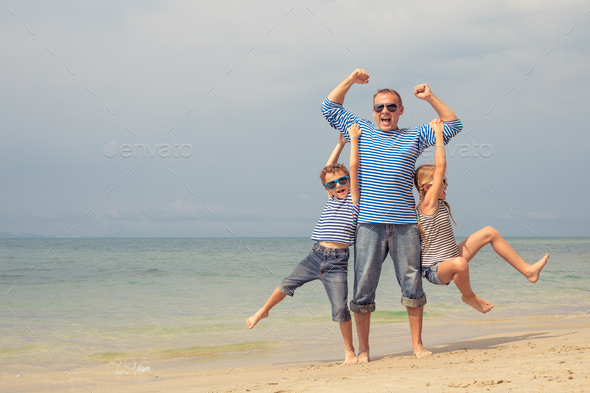 Father and children  playing on the beach at the day time. - Stock Photo - Images