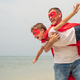 Father and son playing superhero on the beach at the day time. - PhotoDune Item for Sale