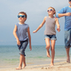 Father and kids running on the beach at the day time. - PhotoDune Item for Sale