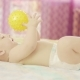 A Beautiful Baby Lies on His Back. He Holds the Ball in His Hand and Plays with It - VideoHive Item for Sale