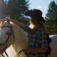 A Young Girl in a Cowboy Hat Takes Care of and Caresses a Horse on an Animal Farm on a Hot Summer - VideoHive Item for Sale