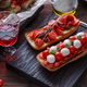 Bruschetta with tomato, basil and mozzarella cheese on wooden board. Traditional italian appetizer - PhotoDune Item for Sale