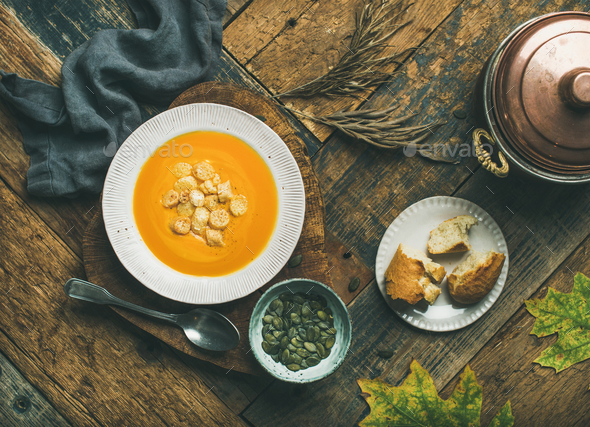 Warming pumpkin cream soup with croutons and seeds - Stock Photo - Images
