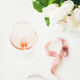 Rose wine in glass, pink decorative ribbon, peony flowers - PhotoDune Item for Sale