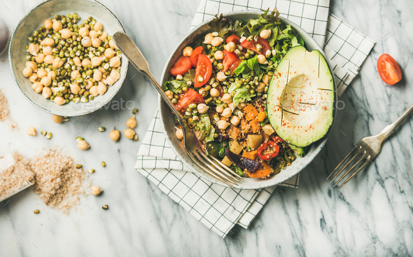 Flat-lay of vegan dinner bowl with avocado, grains, beans, vegetables - Stock Photo - Images