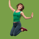 Freedom in moving. Pretty young woman jumping against orange background - PhotoDune Item for Sale