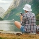 A Woman Uses a Smartphone on the Shore of a Picturesque Fjord in Norway - VideoHive Item for Sale