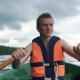 A Young Man in a Boat Rowing Wooden Oars on the Water. Life Jacket on the Body of a Man. - VideoHive Item for Sale