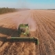 Aerial Drone Shot of a Combine Harvester Working in a Field at sunset.Harvesting - VideoHive Item for Sale
