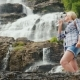 Active Woman Drinks Clean Water Against the Background of the Twindefossen Waterfall in Norway - VideoHive Item for Sale