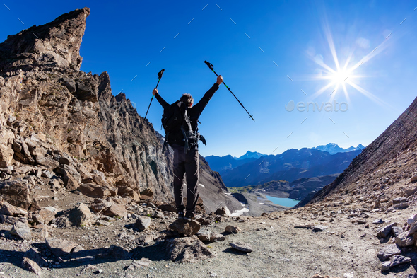 Hiker reaches a high mountain pass - Stock Photo - Images