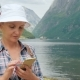 An Active Woman Uses a Smartphone on a Fjord in Norway. Always in Touch, Technology on the Road - VideoHive Item for Sale
