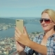 Woman Tourist Taking Pictures of Herself Against the Background of the City of Bergen in Norway - VideoHive Item for Sale