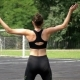 Back View on Young Athlete Woman in Sport Outfit Engaged in Fitness on the Sports Field in the Park. - VideoHive Item for Sale