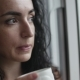 Pensive Young Caucasian Woman Looking at the Rain Outside the Window Drinking Coffee - VideoHive Item for Sale