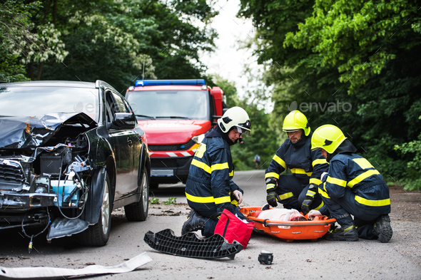 Firefighters helping a young injured woman after a car accident. - Stock Photo - Images