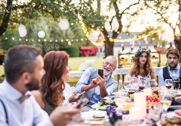 A senior man taking selfie at the wedding reception outside in the backyard. - Stock Photo - Images