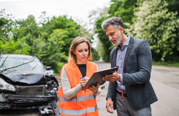 An insurance agent talking to a woman outside on the road after a car accident. - Stock Photo - Images