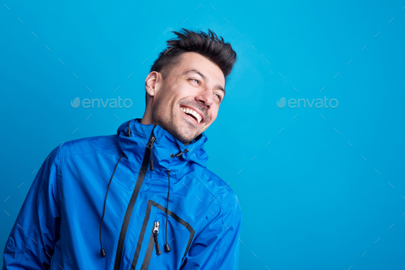Portrait of a young laughing man in a studio with anorak on a blue background. - Stock Photo - Images
