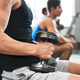 Unrecognizable young fit men in gym exercising with dumbbells. - PhotoDune Item for Sale