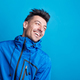Portrait of a young laughing man in a studio with anorak on a blue background. - PhotoDune Item for Sale