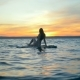 Slim Dark-haired Lady Is Sitting on a Drifting Paddleboard - VideoHive Item for Sale