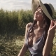 Young Beautiful Woman in a Straw Hat Sits in a Wheat Field and Enjoys a Warm Summer Day - VideoHive Item for Sale