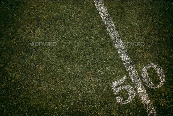 Football field ground fifty yard line. Friday night lights. Stock Photo by fruitcocktail