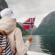 A Tourist with a Flag of Norway Stands on the Nose of a Cruise Ship. Journey Through the Picturesque - VideoHive Item for Sale