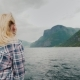 A Romantic Woman on the Bow of the Ship, Sailing Along the Beautiful Fjord. The Wind Blows Into Her - VideoHive Item for Sale