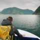 A Man with a Backpack Travels Through a Picturesque Fjord in Norway - VideoHive Item for Sale