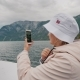 A Woman Takes a Beautiful View of the Fjord in Norway, Sails on a Small Cruise Ship - VideoHive Item for Sale