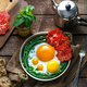 Sunny side fried eggs in a copper pan with tomatoes and green beans, copy space. - PhotoDune Item for Sale