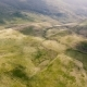 Aerial Shot of a Carpathian Valley with Salad and Rusty Grass Patches in Summer - VideoHive Item for Sale
