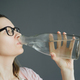 woman in glasses drinks water from glass bottle - PhotoDune Item for Sale