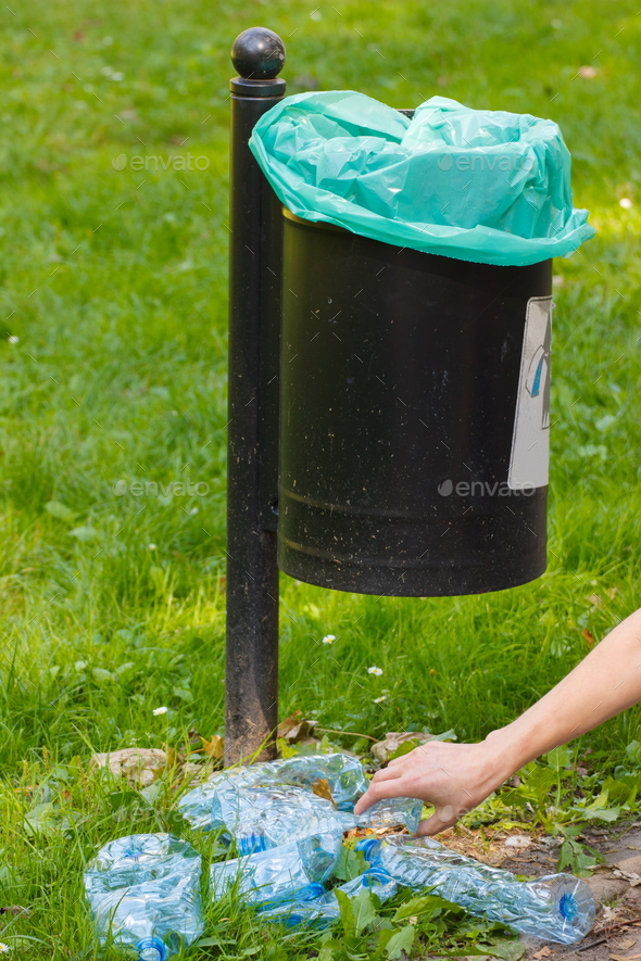Trash can in park and heap of plastic bottles, littering of environmental concept Stock Photo by ratmaner