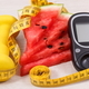 Glucose meter for checking sugar level, portion of watermelon, centimeter and dumbbells - PhotoDune Item for Sale