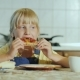 A Little Girl with an Appetite Eating Pizza in the Kitchen - VideoHive Item for Sale