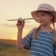 A Girl with Pigtails and a Hat Playing with a Wooden Airplane at Sunset - VideoHive Item for Sale