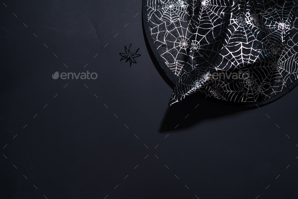 Black witch hat with a pattern of cobwebs on black background - Stock Photo - Images