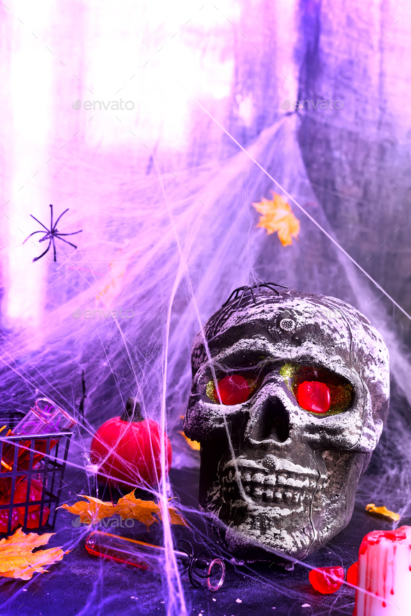 Still life with human skull and autumn leaves, spider on black violet Panton halogen background - Stock Photo - Images
