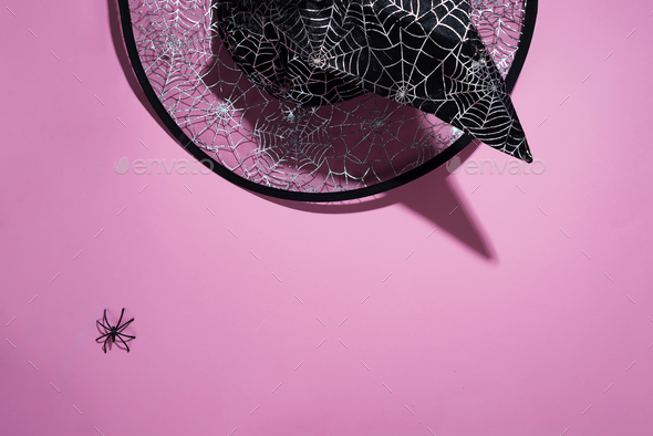 Black witch hat with a pattern of cobwebs and spider on pink background, flat lay with copy space - Stock Photo - Images