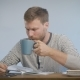 Young Man with Beard Drinking Coffee and Reading Magazine in the Kitchen in the Morning - VideoHive Item for Sale