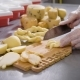 Worker of a Cheese Factory Slicing Fresh Cheese with a Knife Wearing Special Gloves - VideoHive Item for Sale