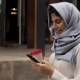 Young Woman in Hijab Drinking a Coffee To Go and Looking at Smartphone - VideoHive Item for Sale