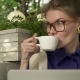 Hipster Girl in Glasses Drinking Coffee in Summer Cafe Near Her Laptop - VideoHive Item for Sale