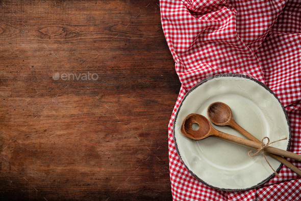 Empty plate, kitchen utensils and red tablecloth on wooden