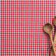 Wooden kitchen utensils on red checkered picnic tablecloth, top view, copy space - PhotoDune Item for Sale